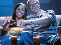 Couple sitting on sofa watching television with bowl of popcorn smiling