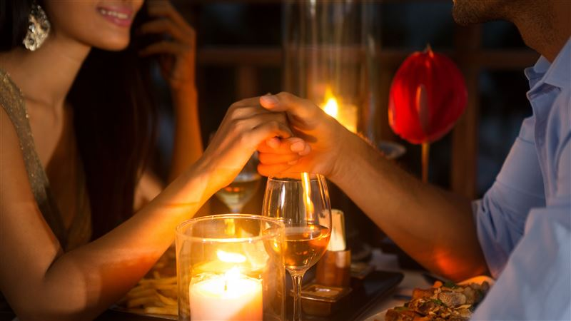 Romantic couple holding hands over candlelight on valentine's day