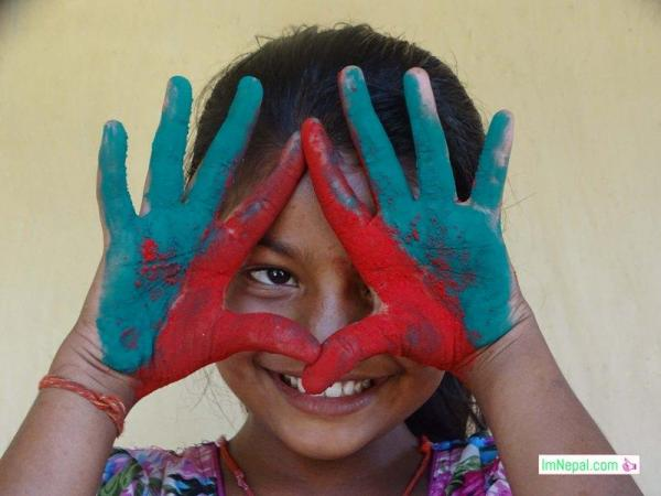 Holi girl - a little girl is showing her hands making love sign with colors