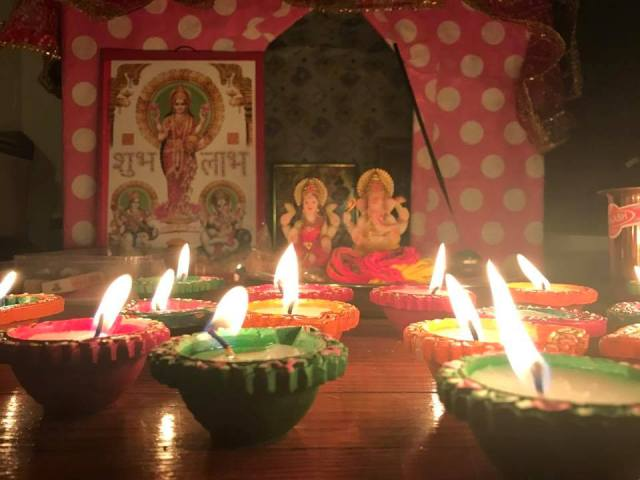 Diwali diya lamps lights in front of Lord Ganesha and Goddess Lakshami Image