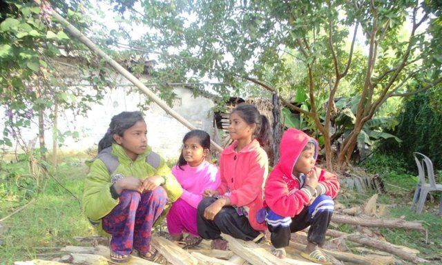 children are siting on the firewood - poor poverty in Nepal