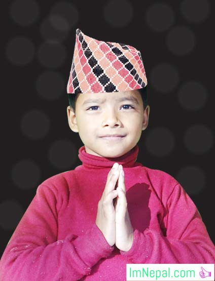 Small Nepali boy saying Namaste Hello in a dhaka topi