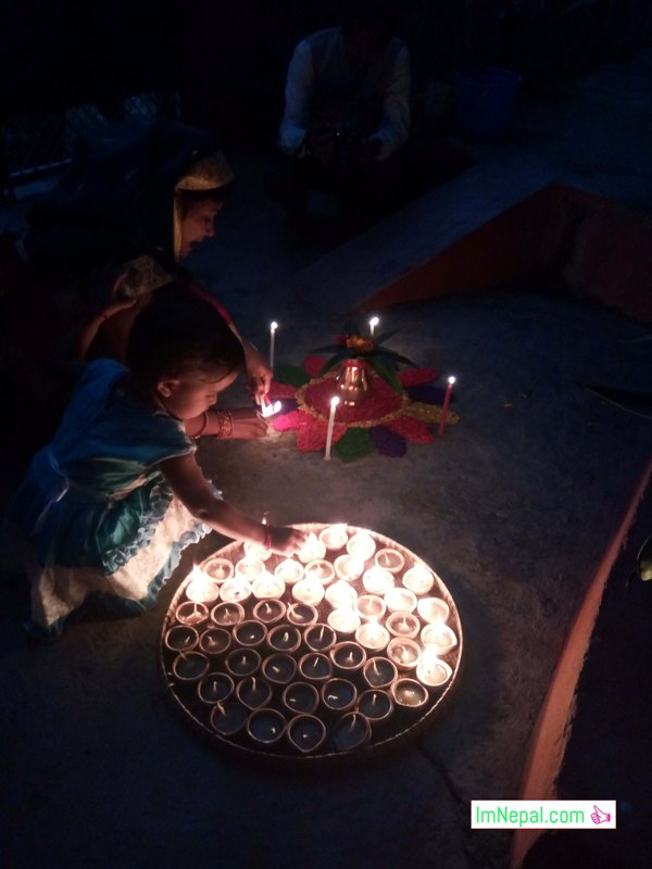 A little daughter with her mother is lightening the Diya Diyo in Diwali tihar Deepavali festival