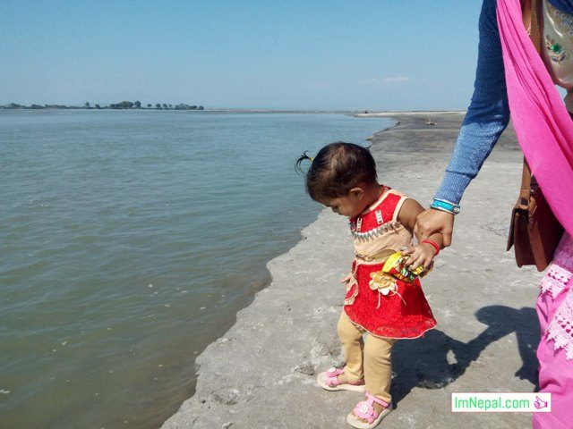 a little daughter with her mother in the river bank, Koshi Nepal