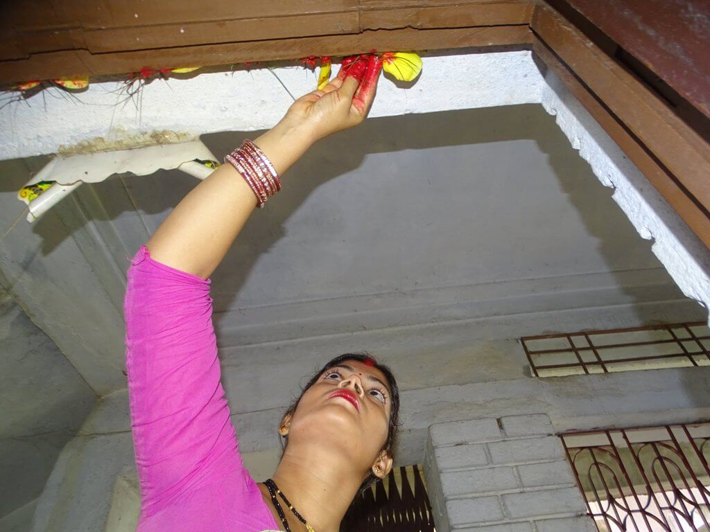 Nepalese woman Decorating Door Home