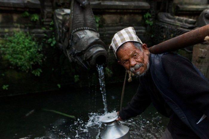 newar man in kathmandu nepal watering Most Beautiful City in Nepal